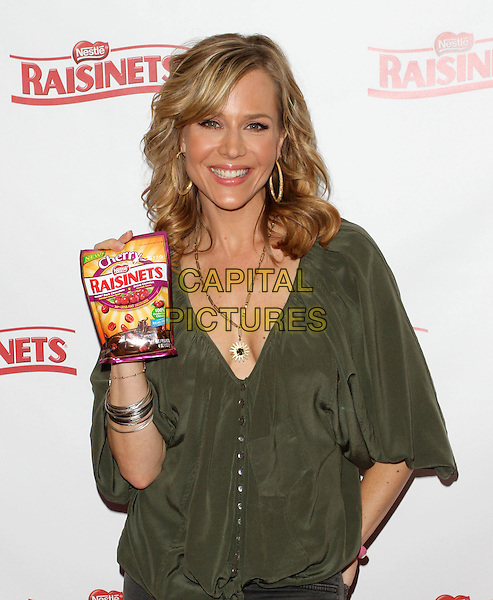 JULIE BENZ.Julie Benz Visits Gifiting Services held at Gifiting Services Showroom, Los Angeles, CA, USA..October 26th, 2010.half length green top low cut v-neck neckline necklace hand in pocket gold hoop earrings raisinets silver bracelets .CAP/ADM/FS.©Faye Sadou/AdMedia/Capital Pictures.