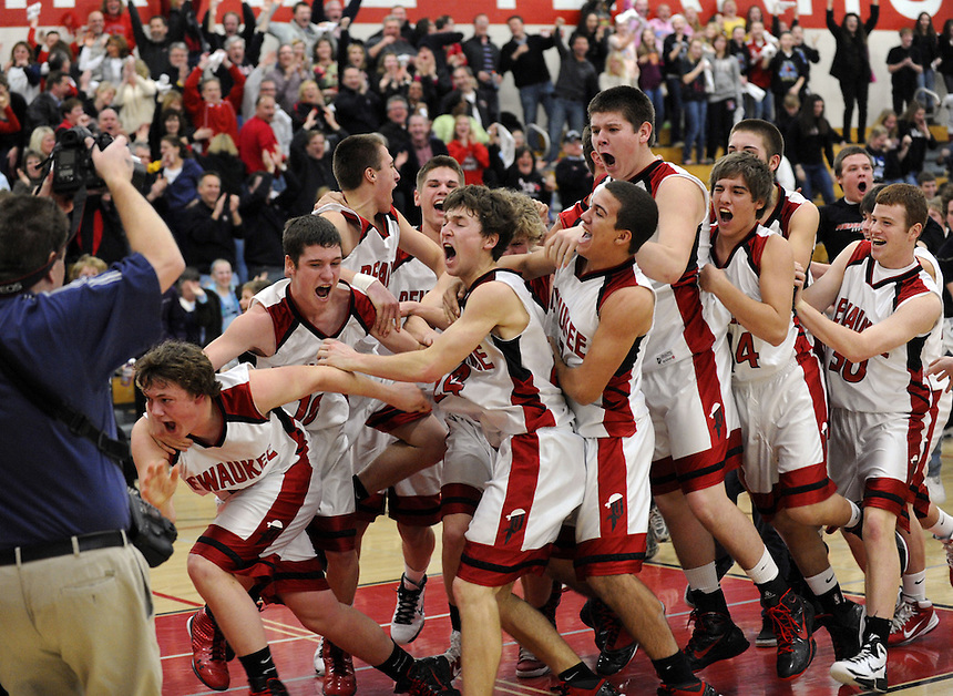 Pewaukee basketball team members mob Dave Reese (in front, third from left) after he made a last second 3-point basket to win the game against Catholic Memorial at Pewaukee on Tuesday, March 1, 2011. Ernie Mastroianni photo.