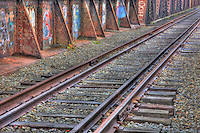 Railroad tracks and graffiti covered deck leading to the historic Free Black Bridge, a through truss pin-connected bridge over the Androscoggin River on the Maine Central Railroad in Brunswick, Maine
