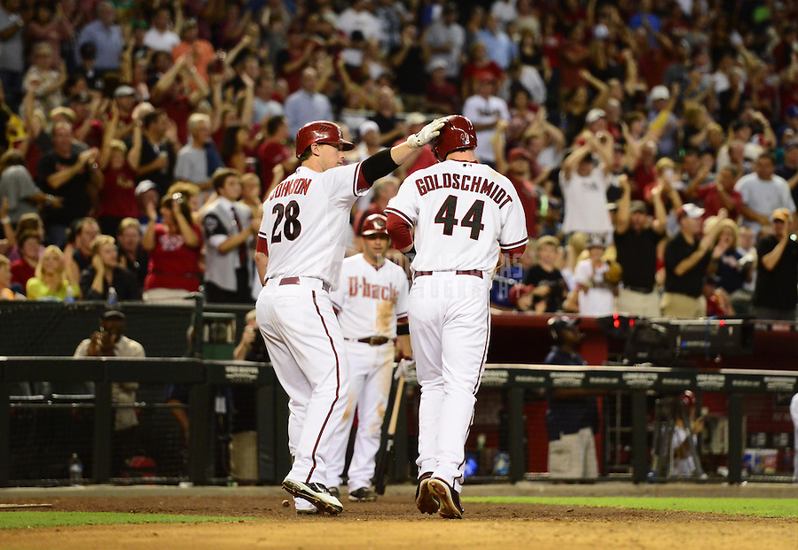 Sept. 11, 2012; Phoenix, AZ, USA: Arizona Diamondbacks first baseman (44) Paul Goldschmidt is congratulated by teammate Chris Johnson after scoring against the Los Angeles Dodgers in the seventh inning at Chase Field. Mandatory Credit: Mark J. Rebilas-