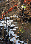 WATERBURY, CT-012118JS05--Workers from Kropp Environmental Contractors, clean up oil in the Naugatuck River following an oil spill from Somers Thin Strip Company on Piedmont Street in Waterbury. Approximately 4,000 gallons of hydraulic oil leaked from a faulty valve. <br /> Jim Shannon Republican-American