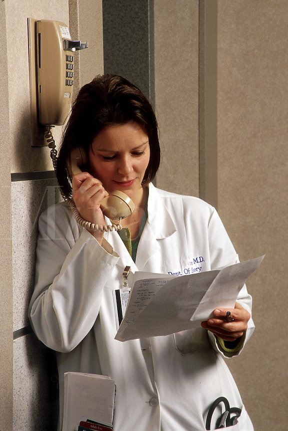 Female medical resident talking on a hospital telephone while reviewing notes.