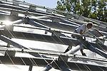 Foto: VidiPhoto<br /> <br /> ARNHEM &ndash; De bekende decorateur Madelief van Wissen uit Helouw (Gld) gaat dinsdag de boot in om de spuitbetonnen bomen in de nieuwe Mangrove van Burgers&rsquo; Zoo van een &lsquo;echtsheidskenmerk&rsquo; te voorzien. Tot na de opening van 12 juli is de kunstenares, die ook de Efteling &lsquo;smoel&rsquo; geeft, nog bezig in de 3000 vierkante meter grote hal in Arnhem. Tot die tijd zijn ook de andere uitvoerders nog volop bezig met het afbouwen en inrichten van het grootste overdekte mangrovegebied ter wereld. Omar Figueroa, Belizaans Minister of State van Landbouw, Visserij, Bosbouw, Milieu en Duurzame Ontwikkeling, verricht de op 12 juli de offici&euml;le openingshandeling. In Burgers&rsquo; Mangrove komen zeekoeien, wenkkrabben, vlinders, vogels en vissen. Het complex is 16 meter hoog en in eigen beheer gebouwd. Voor het enorme bassin van de Caribische zeekoeien is 2000 kuub grond uitgegraven. Daarin komt straks 1 miljoen liter water. De bouwkosten bedragen 5 miljoen euro. Foto: De laatste werkzaamheden aan de dakspanten aan de buitenzijde.