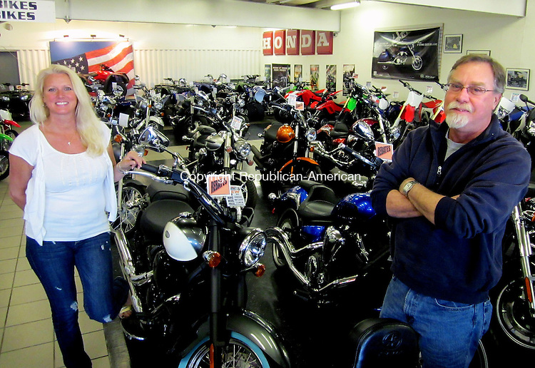 CHESHIRE, CT - April 17, 2013 - 041813LX01 - Carolyn Vallone, (left) and Jim Tabor (right) stand in the center of their Willow's Motorsports showroom in Cheshire. They are selling their business.