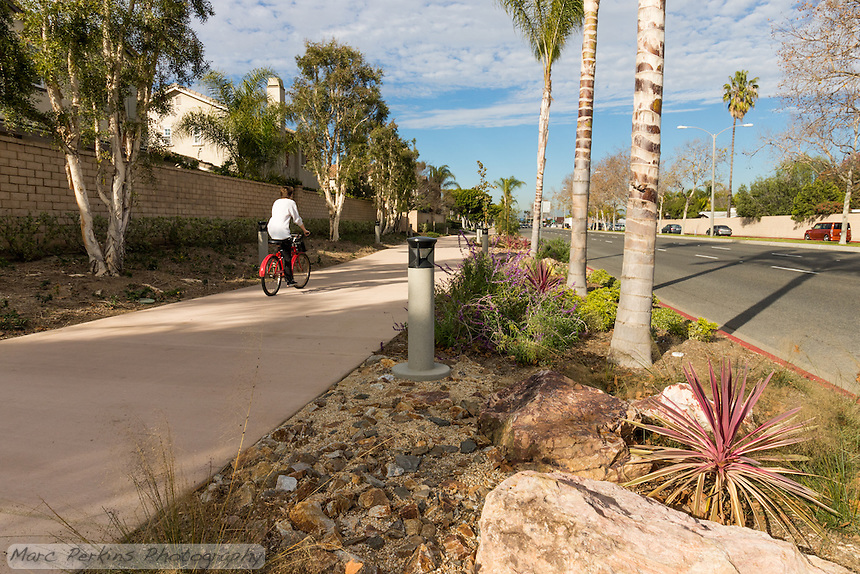 A casual cyclist carrying items in a handlebar basket rides away from the camera along the Harbor Boulevard Cornerstone Bike Trail in Costa Mesa, California under a blue sky dotted with partial clouds.  The woman is on a red city bike with fenders; a very practical commuter setup.  The landscape architecture work on the project was done by David Volz Design.