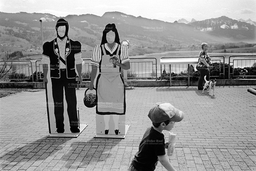 Switzerland. Canton Fribourg. Avry-devant-Pont. The Gruyère restoroute is the perfect place for a break in a lush green landscape with a fantastic view on the Gruyère lake and the swiss Prealps. Swiss Prealps are the northernmost section the Western Alps. A young boy eats a sandwich and runs in front of two dummies used by tourists for environmental photo sessions. Both lay-figures portray a couple, a herder and his wife dressed with traditional clothes. The herders, known as armaillis, allow the cows to graze on the rich grasses found on the sunny mountain slopes. Swiss alpine farmers. Alps mountains peasants. An elderly woman with a dog on a leash. info@didierruef.com<br /> +41 79 691 20 70<br /> www.didierruef.com © 2013 Didier Ruef