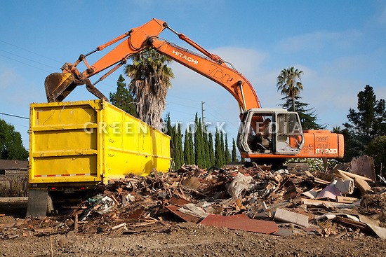 An excavator loading demolition debris of a single family house into a container truck. The materials will be transported to the Zanker Road Landfill where it will be sorted to recyclable wood, concrete, gypsum, and metal waste materials. Cupertino, California, USA