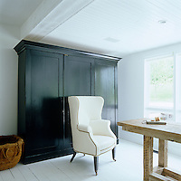 In a corner of the breakfast room a large black lacquered antique cupboard takes up much of the wall space