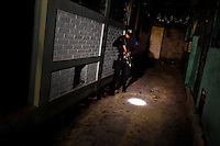 A policeman from the special anti-gang unit (Unidad Antipandillas) patrols during a night raid in Soyapango, a gang neighborhood in San Salvador, El Salvador, 13 December 2013. Although the murder rate in the country has dropped significantly, after a truce between two major street gangs (Mara Salvatrucha and Barrio 18) was agreed in 2012, the lack of security and violence are still the main issues in people's daily life. Due to the fact the gangs have never stopped their criminal activities (extortions, distribution of drugs and kidnappings), the Police anti-gang forces keep running their operations and chasing the 'homeboys' (how the gang's foot soldiers usually call themselves) in the poor, socially deprived suburbs of Salvadoran cities.