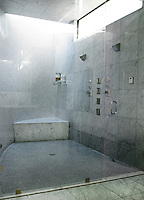 The large wet room is tiled in large grey marble wall tiles and small silvery mosaic ones