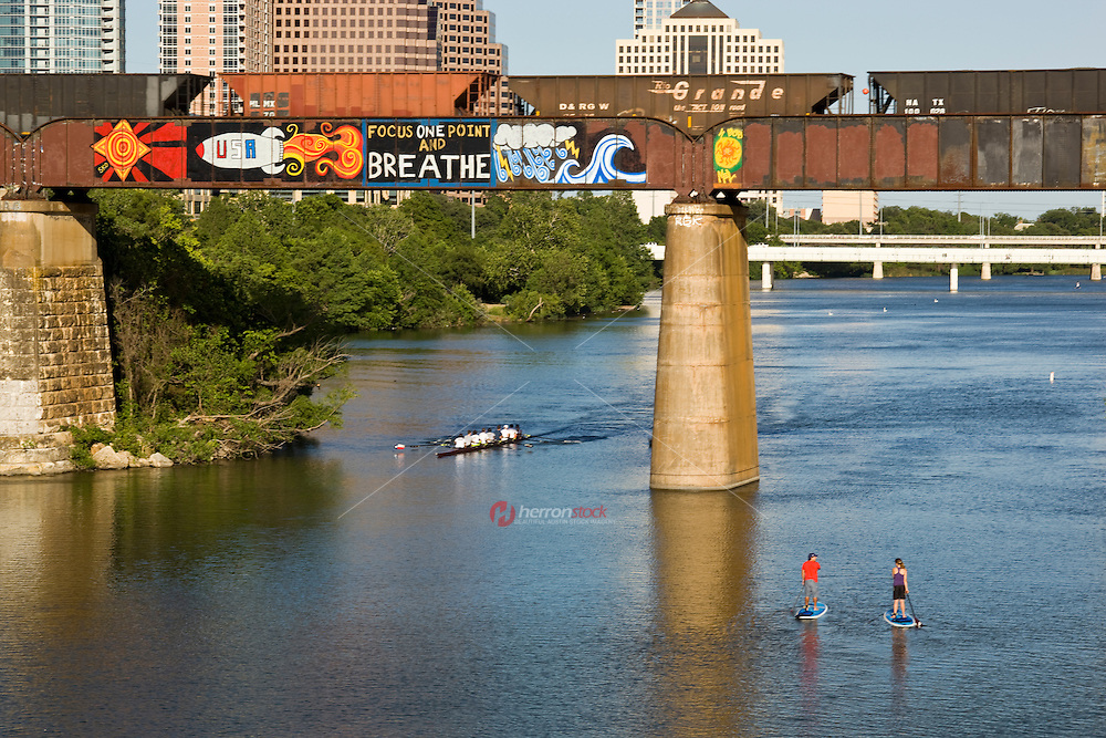 """Focus One Point And Breathe"" with a USA space rocket is a famous and beloved inspirational graffiti painting on a the railroad bridge over Lady Bird Lake, overlooking the Austin skyline."