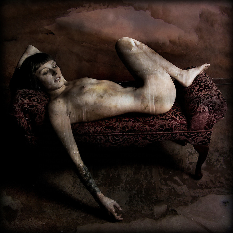 A conceptual image of a young nkaed woman reclining on a sofa