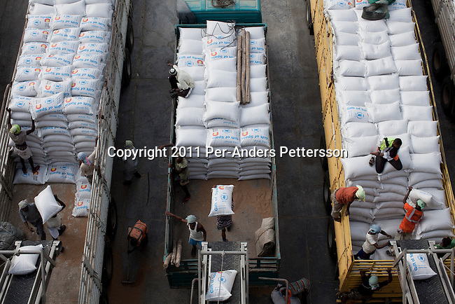 DJIBOUTI, DJIBOUTI - AUGUST 4: Long distance trucks are loaded with 800 bags of wheat each bound to Ethiopia from WFP, World Food Program storage facility in the Djibouti port on August 4, 2011 out Djibouti, Djibouti. A severe drought has added to the misery and hardship in the Horn Of Africa. Many refugees has fled Somali and arrived in Kenya, Ethiopia and Djibouti. A Russian Vessel hired by WFP arrived with 40,000 tons of wheat. The wheat is pumped out and put into bags that weigh fifty kilograms each.  (Photo by Per-Anders Pettersson)