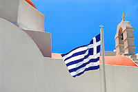 The Greek flag fly's over the Island of Mykonos. The red domes and bell towers of the countless churches dot the labyrinthine of narrow alleyways