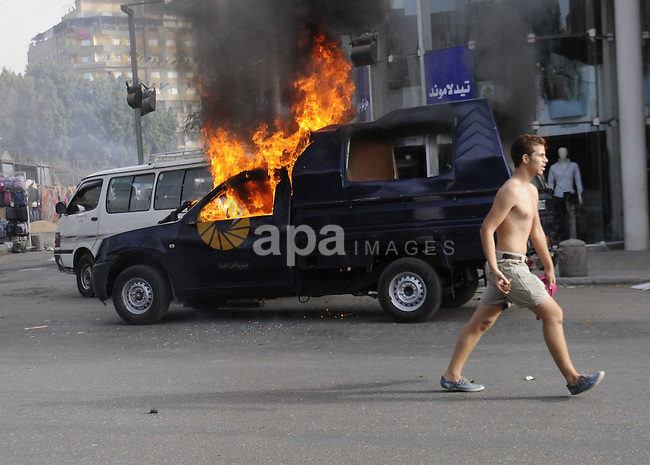 An Egyptian protester shouts slogans in front a burning police car in front of al-Zamalek football club's headquarters in Cairo on Sept. 19, 2013. Members of a hardcore group of fans of the Zamalek football club, the Ultra White Knights (UWK), stormed the club's headquarters in Cairo on Thursday following a protest demanding changes to the club's leadership. Photo by Ahmed Asad
