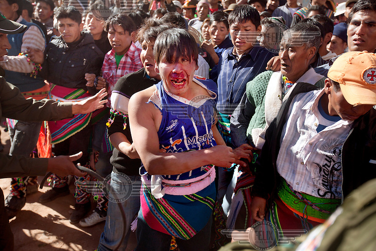 People participate in ritual fighting in the plaza of Macha. <br /> <br /> The people of Macha and surrounding communities carry on the pre-Columbian tradition of ritual fighting. The communities gather on the plaza of Macha to fight and dance in competition with each other. The blood that is spilled is an offering to Mother Earth. In return, the people ask for rain and a good harvest. This ritual is called tinku or fiesta de la cruz since the cross is also engaged in the festivities. The cross is dressed up, given offerings and brought from communities around Macha to the church in town. This syncretic festival melds pagan, pre-christian rituals with Catholic practice. /Felix Features