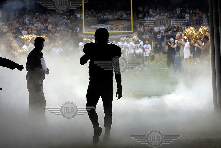 Drew Brees, the quarterback for the New Orleans Saints, walks onto the field in the American Football match against the San Francisco 49'ers.