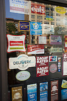 Stickers promoting various crowdsourcing review sites and delivery services are seen on the door of a restaurant in New York on Friday, August 24, 2012. (© Richard B. Levine)