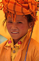 Young Burmese Girl, all dressed in orange including the umbrella, Northern Myanmar, Burma