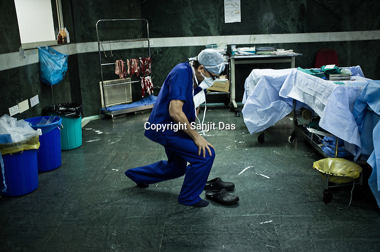 58 year old heart surgeon, Dr. Devi Prasad Shetty stretches after an operation at the Narayana Hrudayalaya in Bangalore, Karnataka, India. Photo: Sanjit Das/Panos