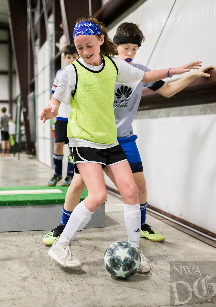 NWA Democrat-Gazette/CHARLIE KAIJO Hailey Crabb, 11, of Bentonville (center) plays a one-versus one with Caleb Crusinbery, 12, of Centerton (right) during a three-day New Year's Soccer Camp, January 4, 2019 at Strike Zone Training Academy in Rogers. <br />