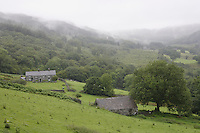 View of the stone cottage against the rain-soaked green hills of the Welsh valley