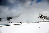 USA, Wyoming, Yellowstone National Park, park visitors walk along the Excelsior Geyser Crater loop in the winter, steam from the Excelsior Geyser Crater in the distance, Midway Geyser Basin