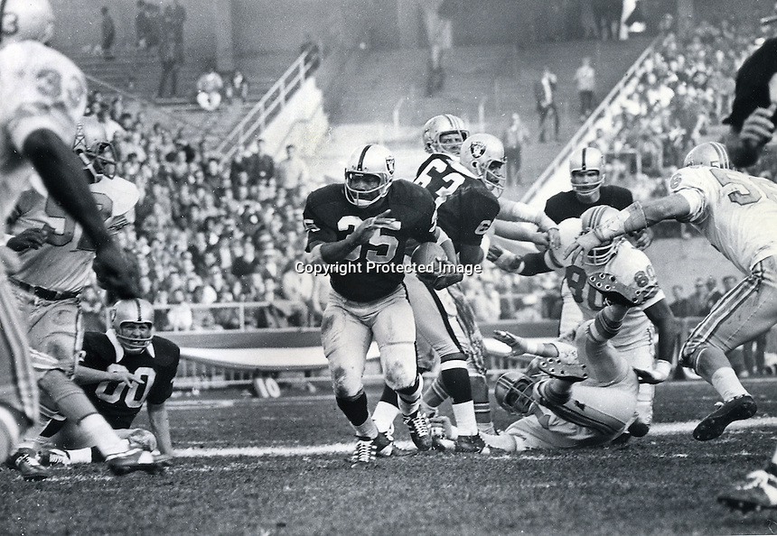 Oakland Raider fullback Hewritt Dixon runs threw a big hole ion t he Houston Oilers line behind blocks by Jim Otto and Gene Upshaw.<br />