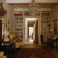 The corridor leading from the entrance hall is framed by a wall of books