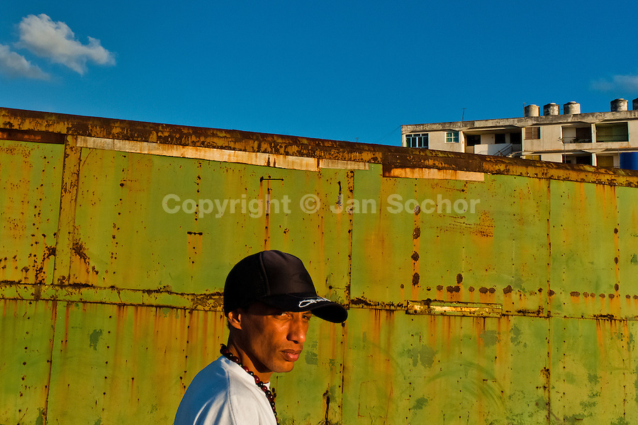 "A young Cuban man, wearing a baseball cap, walks in front of a rusty container in Alamar, a public housing complex in the Eastern Havana, Cuba, 9 February 2009. The Cuban economic transformation (after the revolution in 1959) has changed the housing status in Cuba from a consumer commodity into a social right. In 1970s, to overcome the serious housing shortage, the Cuban state took over the Soviet Union concept of social housing. Using prefabricated panel factories, donated to Cuba by Soviets, huge public housing complexes have risen in the outskirts of Cuban towns. Although these mass housing settlements provided habitation to many families, they often lack infrastructure, culture, shops, services and well-maintained public spaces. Many local residents have no feeling of belonging and inspite of living on a tropical island, they claim to be ""living in Siberia""."