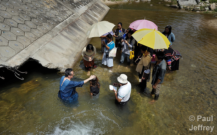 Gary Moon (left), a United Methodist missionary in Thailand, prays with Misae Armo before her baptism in a river near Buyer, a small village in northern Thailand populated by indigenous hill tribe people. Armo is joining the Pranetta United Methodist Church in the community.