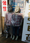 Hong Kong urban scene clothes shop with plastic covered mannequins.