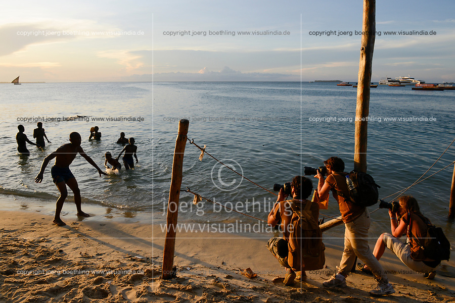 TANZANIA Zanzibar, Stone town, evening at sea, tourist with cameras snaping bathing youngster / TANSANIA Insel Sansibar, Stonetown, abends am Meer, Touristen fotgrafieren badende Jugendliche