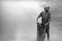 Garimpeiro observa o fundo da cava do garimpo de Serra pelada.<br /> Estima-se que cerca de 120 mil pessoas viveram ali eno auge do garimpo, de 82 a 86. A primeira pepita foi encontrada em dezembro de 79, por um vaqueiro da fazenda do velho Genésio, dono daquelas terras. A fofoca correu e, entre fevereiro e março de 80, mais de 30 mil homens chegaram ao local. A princípio o ouro era só na Grota Rica, um curso dŽágua que dava pepitas na raiz do capim, nem precisava cavar quase nada. Não demorou muito para encontrarem um dos maiores depósitos de ouro do mundo logo ali ao lado, a aberração geológica que conhecemos como Serra Pelada.<br /> Curionópolis, Pará, Brasil.<br /> Foto: Foto: ©Paulo Santos.<br /> 1984.