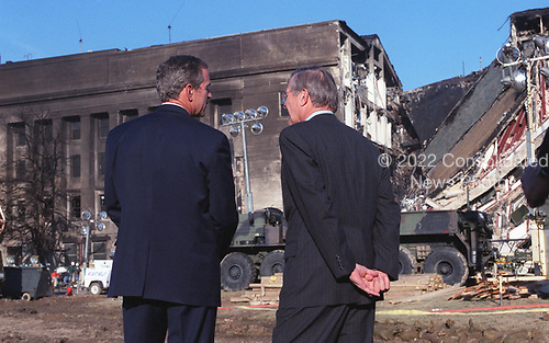 United States President George W. Bush (left), accompanied by US Secretary of Defense Donald H. Rumsfeld (right) look over the scene of destruction at the Pentagon in Washington, DC on September 12, 2001.  On the morning of September 11, an American Airlines flight was hijacked and deliberately crashed into the headquarters of the Department of Defense.  The mid-portion of the western face of the Pentagon took the full brunt of the fuel-loaded passenger jet.  All 64 passengers and crew-members aboard the plane were killed. <br /> Credit: DoD via CNP