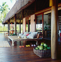 A large Balinese daybed, dining table and bench seats furnish the front deck of the beach house