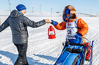 Former Nome resident and Iditarod finisher, Melissa Stewart, gives last place finisher and Red Lantern Award winner Cindy Abbott the red lantern on the outskirts of Nome on her way to the finish line during the 2017 Iditarod on Saturday March 18, 2017.<br /> <br /> Photo by Jeff Schultz/SchultzPhoto.com  (C) 2017  ALL RIGHTS RESERVED