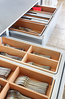 Stainless steel drawers for cutlery and kitchen utensils are lined in maple wood