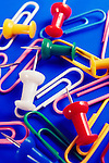 Colorful thumbtacks and paperclips on blue background, office supplies conceptual still life