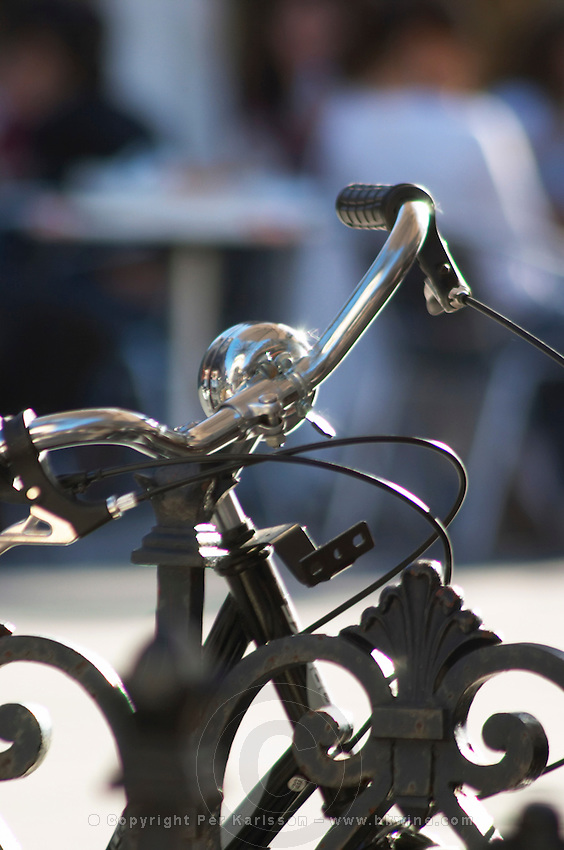 A bicycle parked in the sun and locked to an iron railing with a bell at a cafe in Bordeaux