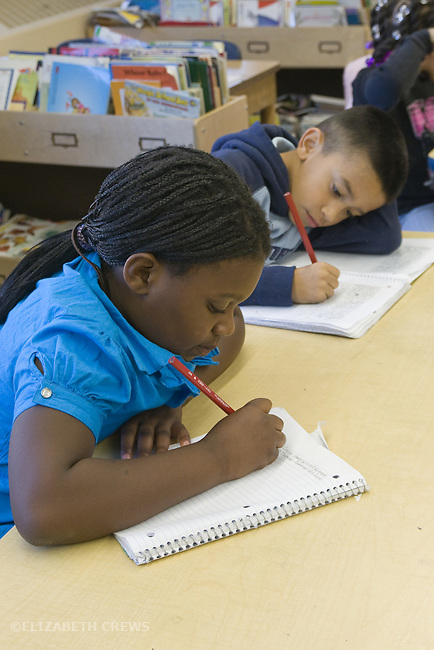 Oakland CA  Second grade students, African American and Latino, working on writing project in class