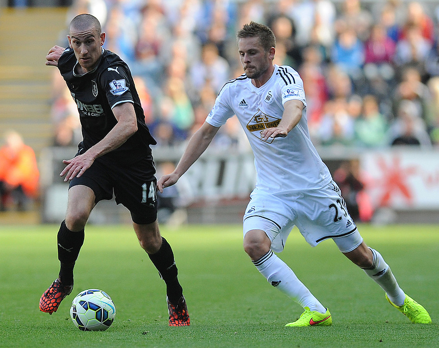 Burnley's David Jones vies for possession with Swansea City's Gylfi Sigur?sson<br /> <br /> Photographer Ashley Crowden/CameraSport<br /> <br /> Football - Barclays Premiership - Swansea City v Burnley - Saturday 23rd August 2014 - Liberty Stadium - Swansea<br /> <br /> &copy; CameraSport - 43 Linden Ave. Countesthorpe. Leicester. England. LE8 5PG - Tel: +44 (0) 116 277 4147 - admin@camerasport.com - www.camerasport.com