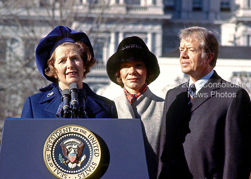 "Washington, DC - (FILE) -- Prime Minister Margaret Thatcher of the United Kingdom, left, is shown as she spoke at the arrival ceremonies in her honor at the White House in Washington, D.C. on Monday,December 17, 1979. In her remarks she praised United States President Jimmy Carter's, right, handling of the Iran hostage crisis by saying he has gained respect around the world for his courage and patience.  First lady Roslyn Carter, center, looks on..Credit: Benjamin E. ""Gene"" Forte - CNP"