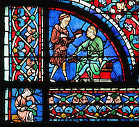 A cobbler shows a shoe to a customer, who removes his own shoe to try it on, part of the donor section of the shoemakers at the bottom of the Glorification of the Virgin stained glass window, in the nave of Chartres Cathedral, Eure-et-Loir, France. This window depicts the end of the Virgin's life on earth, her dormition and assumption, as told in the apocryphal text the Golden Legend of 1260. Chartres cathedral was built 1194-1250 and is a fine example of Gothic architecture. Most of its windows date from 1205-40 although a few earlier 12th century examples are also intact. It was declared a UNESCO World Heritage Site in 1979. Picture by Manuel Cohen