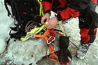 An ice climber prepares his gear before climbing a cliff overlooking Cook Inlet near Ninilchik, Alaska.