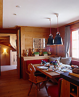 The chalet kitchen has a cosy dining area that has been laid for breakfast and is lit by a pair of pendant lights