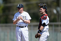 Edgewood Eagles head coach Al Brisack (left) makes a pitching change as catcher Nick Cheaney (30) looks on during the second game of a doubleheader against the UW-Stout Blue Devils on March 16, 2015 at Lee County Player Development Complex in Fort Myers, Florida.  UW-Stout defeated Edgewood 8-2.  (Mike Janes/Four Seam Images)