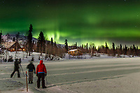 Guests on photo tour at Winter Lake Lodge photograph the Aurora (Northern Lights ) in winter lodge buildings in background.    People. taking pictures