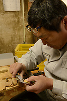 Masahara Nakajima, owner of Nakajima Seikichi Shoten, measuring semi-finished shogi playing pieces. Tendo, Yamagata Prefecture, Japan, February 19, 2018. The city of Tendo in Yamagata Prefecture is famous for its shogi (Japanese chess) playing pieces. Production started early in the 19th century and Tendo still produces over 95% of the Shogi pieces made in Japan.