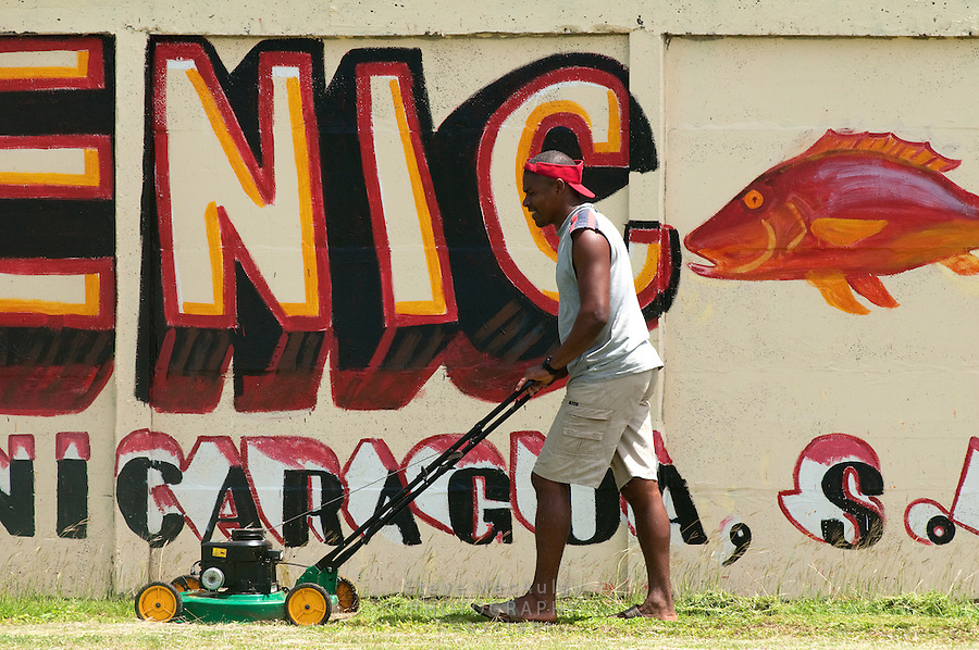 Black man mowing grass, Municipal baseball filed/stadium, Big Corn Island, Nicaragua